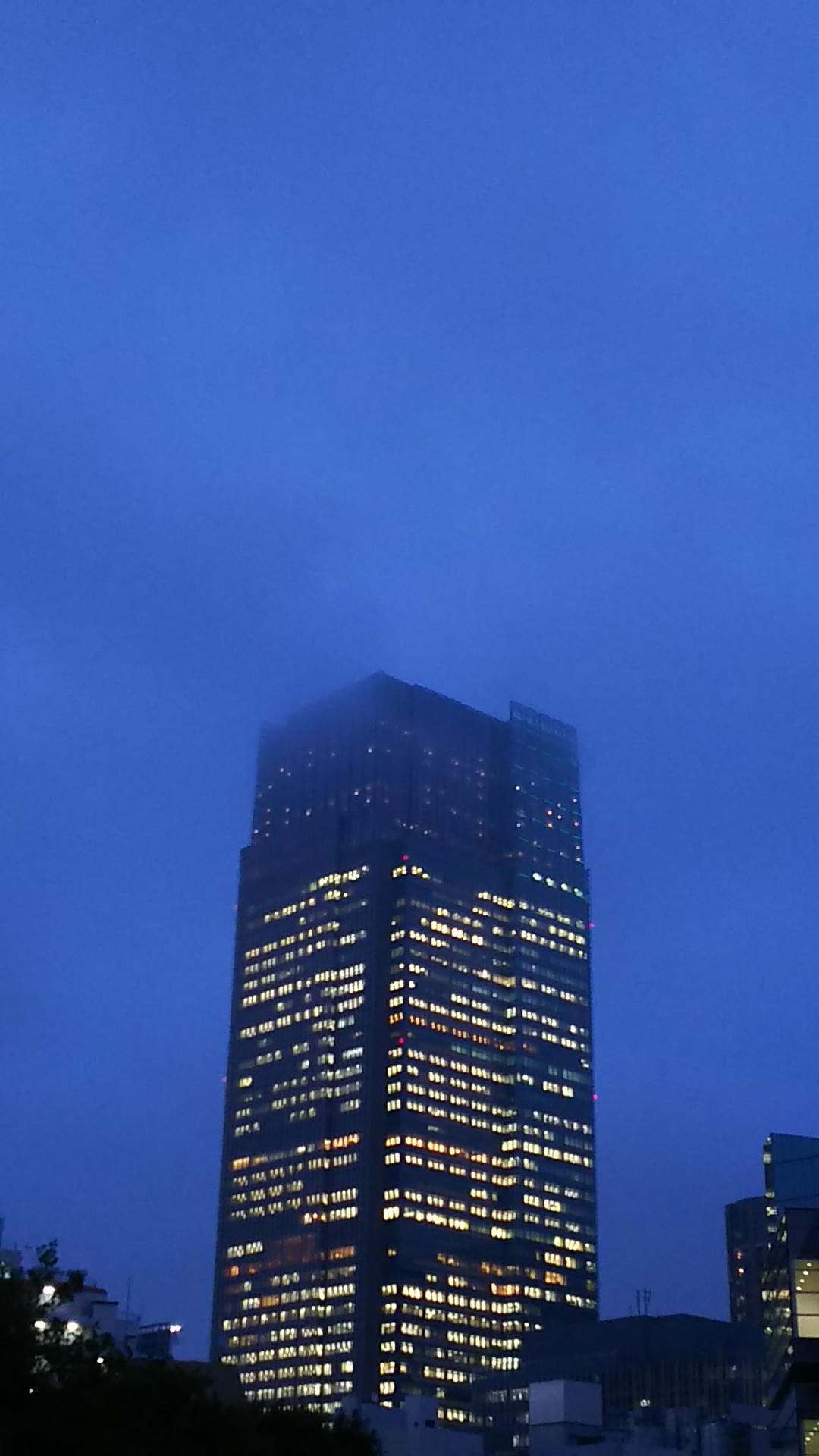 雲で先端が霞むビル