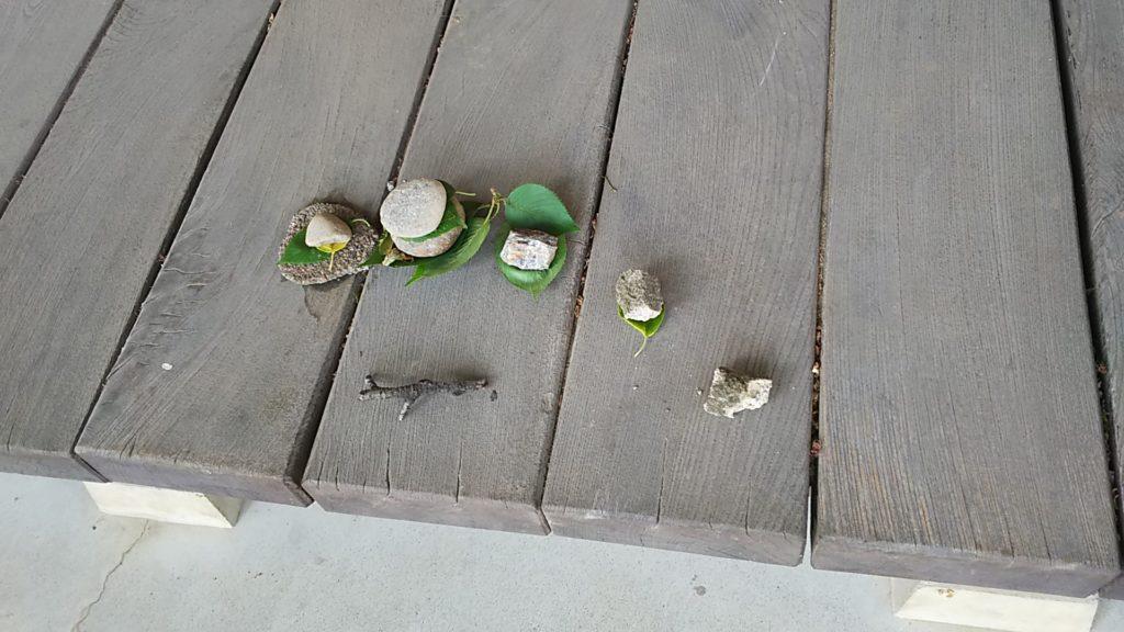 赤烏神社 拝殿の縁に謎の置物。木の枝と小石と葉っぱ。お供え的な?
