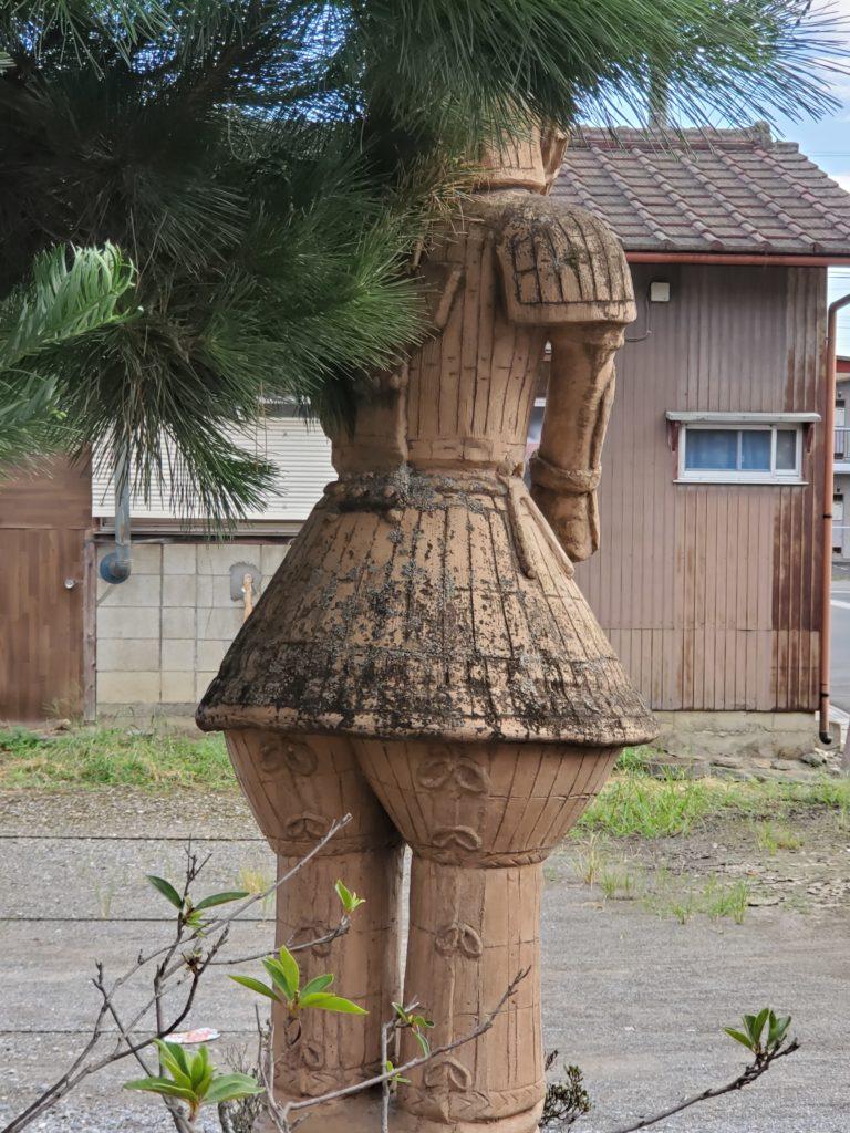 鳥居の横に佇む「埴輪 挂甲武人」のレプリカ、後ろから