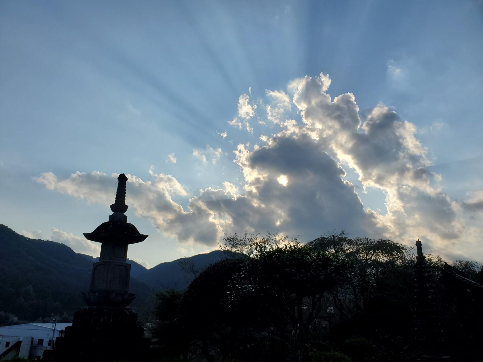 境内から望む、夕日を浴びて後光のように輝く雲